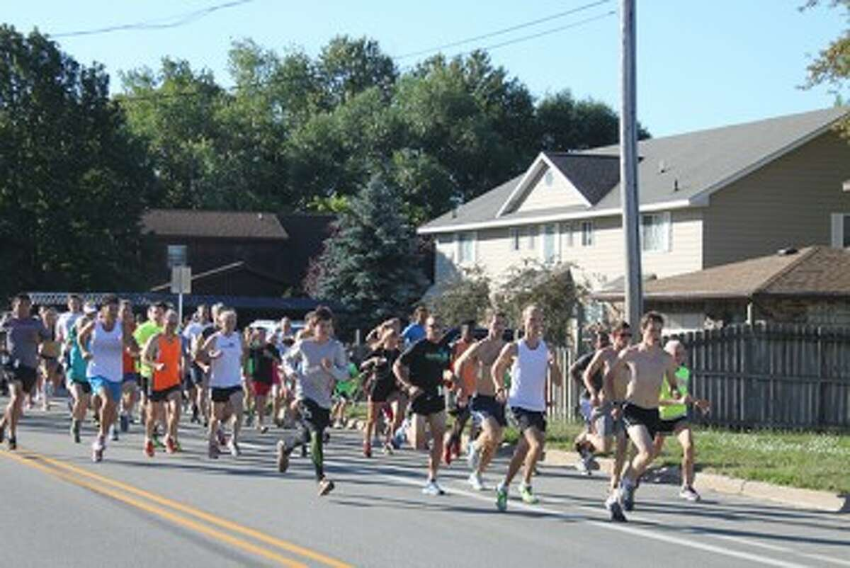 Runners take off from the start of the Onekama Days 5K on Saturday. (Ken Grabowski/News Advocate)