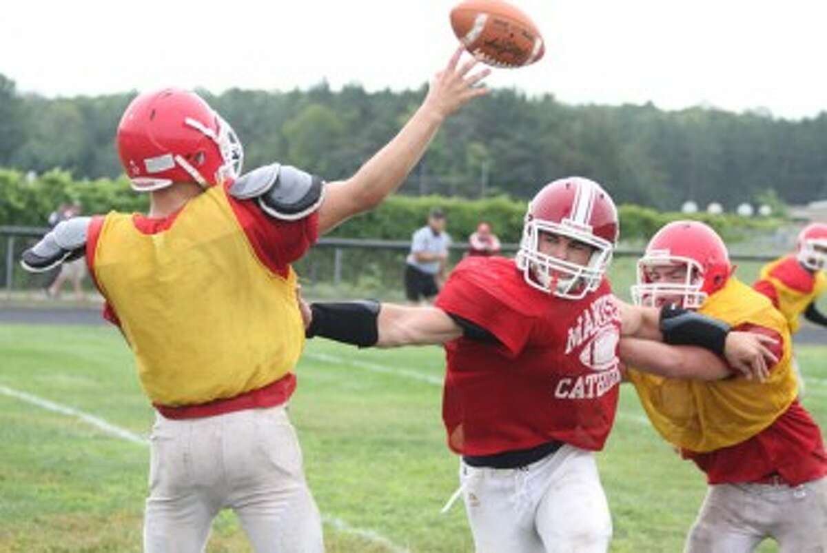 Manistee Catholic Central's Jesse Miller (center) puts pressure on the quarterback during a scrimmage against Benzie Central on Thursday. (Matt Wenzel/News Advocate)