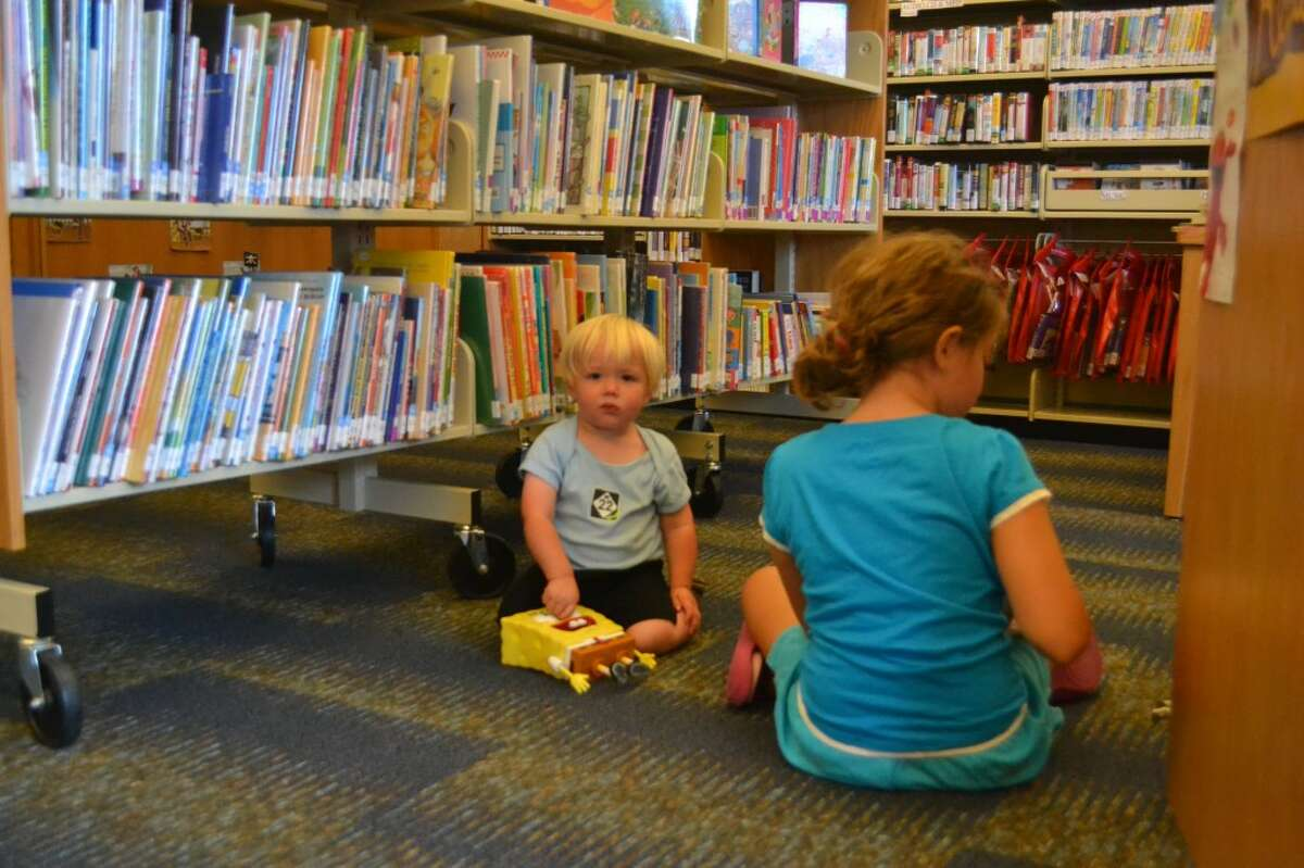 Charlie May (LEFT) and his older sister Grace May (RIGHT) come to the Arcadia Library with their mother every week. (Meg LeDuc/News Advocate)