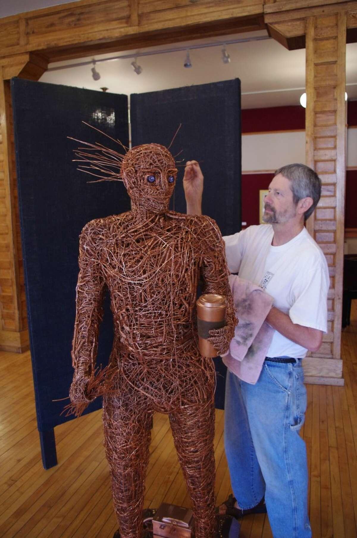 Sculptor Dave Masten touches up his work