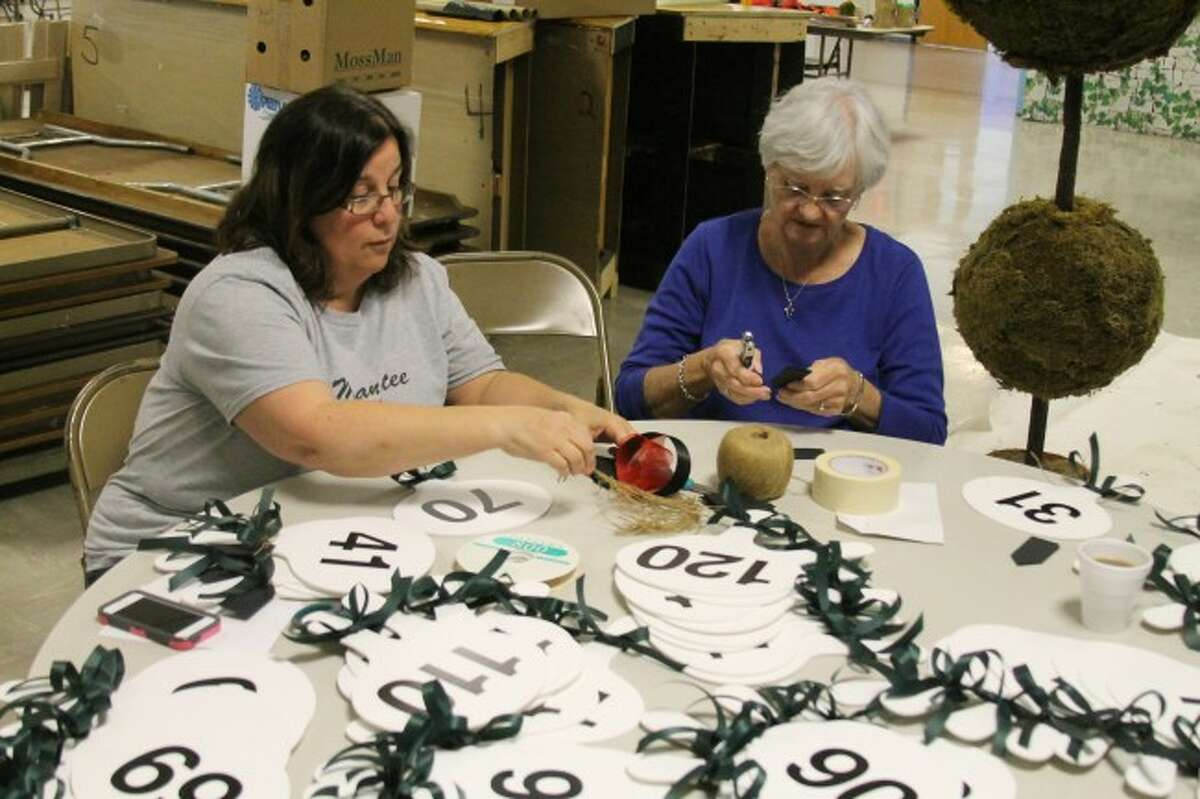 Carol Slivka and Kathy Skiera prepare the numbers that will be used in the silent auction at the HARVEST event on Saturday. The theme for this year will be Run for the Roses based on the Kentucky Derby.