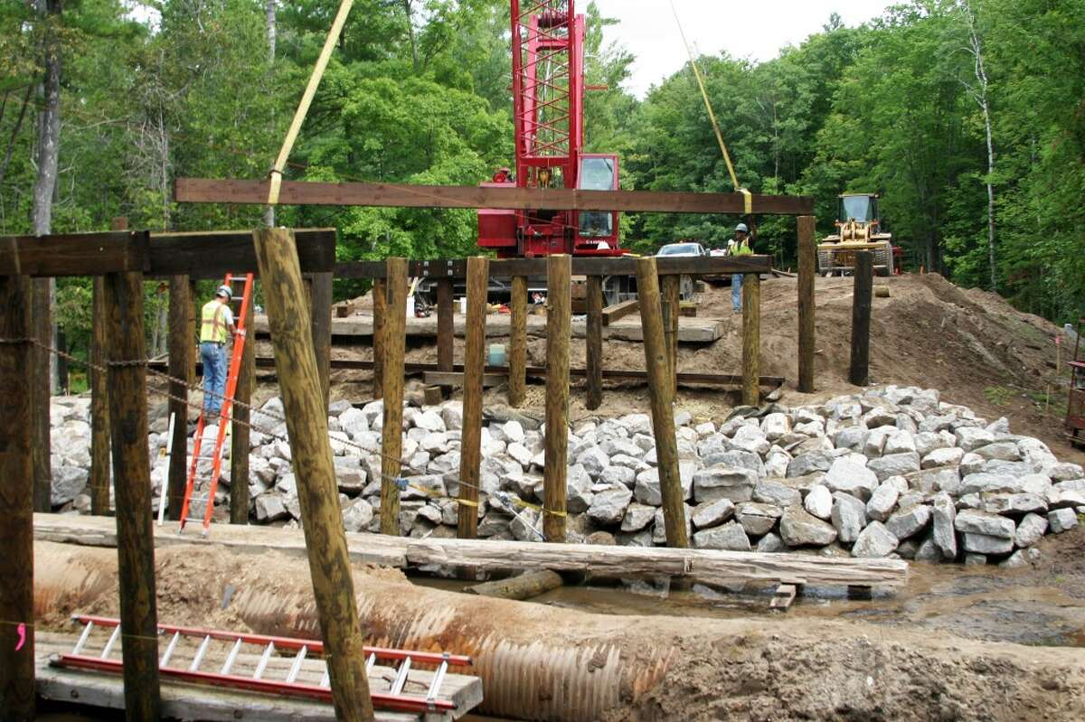 Team Elmer's crew members using a Manitowoc lattice boom crawler crane moves a giant wood beam into place at the Reynolds Road Bridge. Work is expected to completed by Sept. 14. (Roland Halliday/Pioneer News Network)