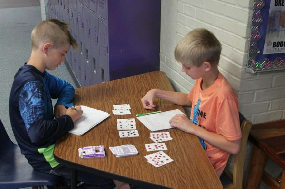 Brethren Elementary School students Alexander Cramer and Tait Young use playing cards to work in a unique exercise to improve their division skills.