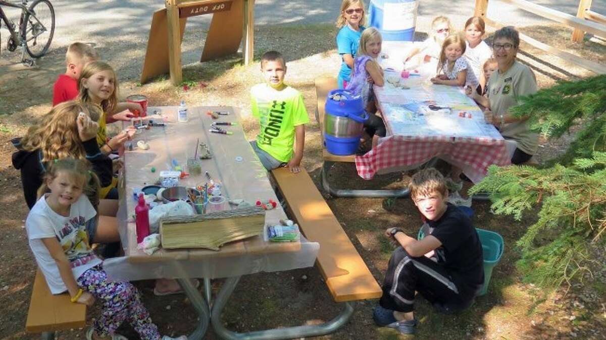 State park campground hosts enjoy free camping while getting the opportunity to engage with guests of all ages in fun activities, such as crafting.