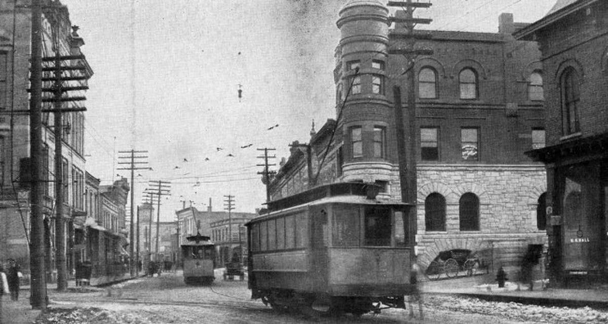 The Manistee, Eastlake, and Filer City railway cars travel down River Street circa late 1890s.