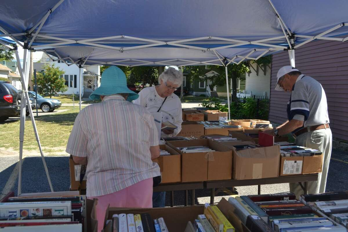 Residents browse tables full of books during the Friends of Manistee County Library book fair on Saturday. (Meg LeDuc/News Advocate)