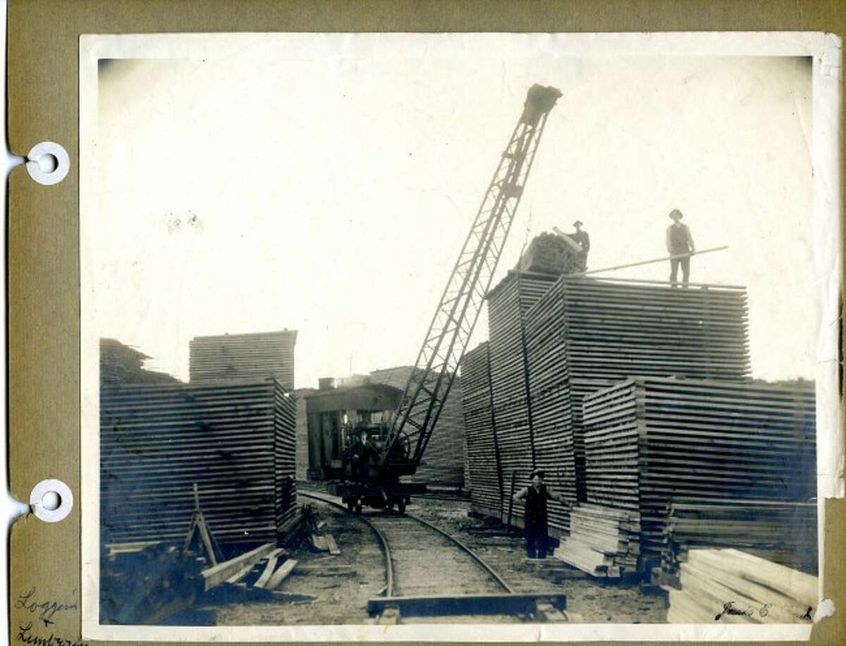 One of the local lumber mills is shown with an abundance of wood in this early 1900s picture.