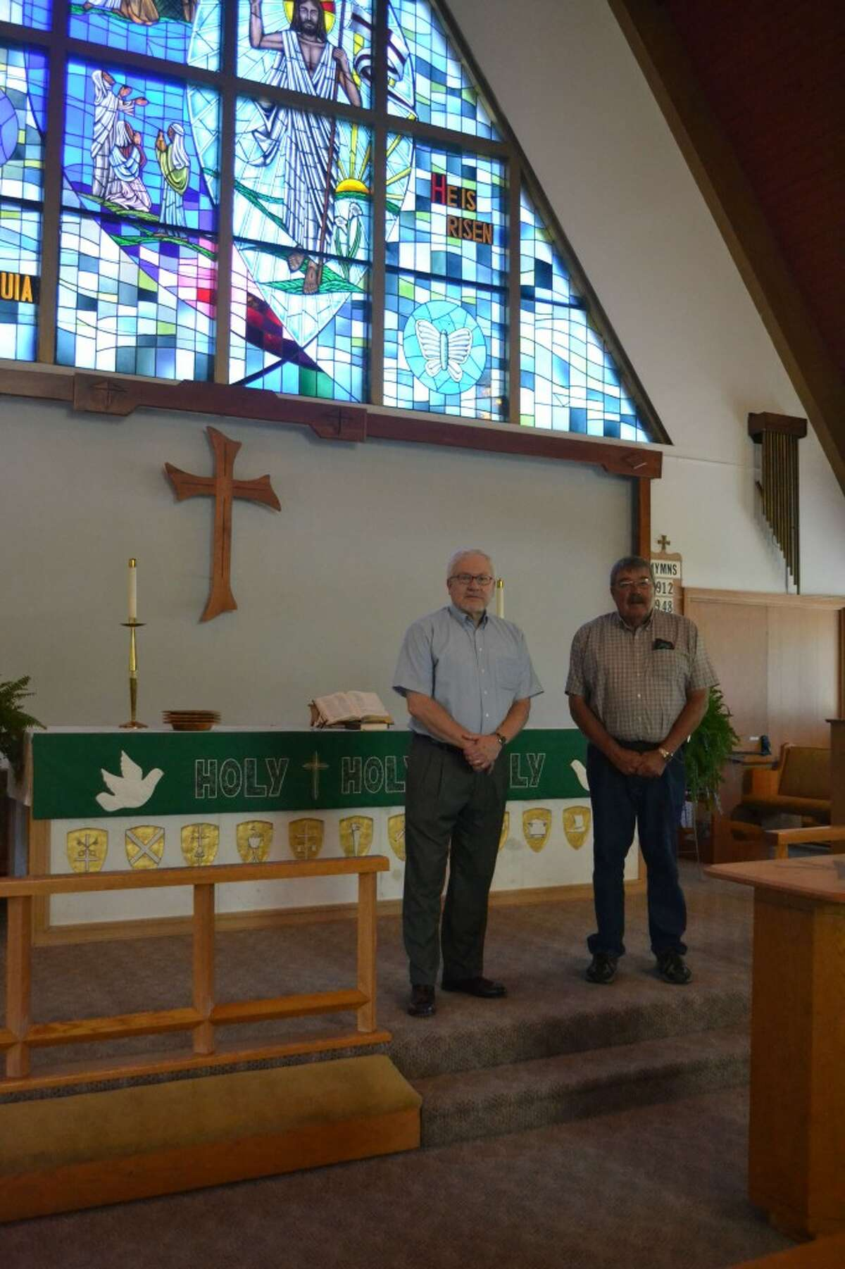 Rev. Ainslie Wagner (LEFT) and elder Joel Meister (RIGHT) guided the congregation of Trinity Lutheran of Onekama as parishioners decided to relight the cross. (Meg LeDuc/News Advocate)
