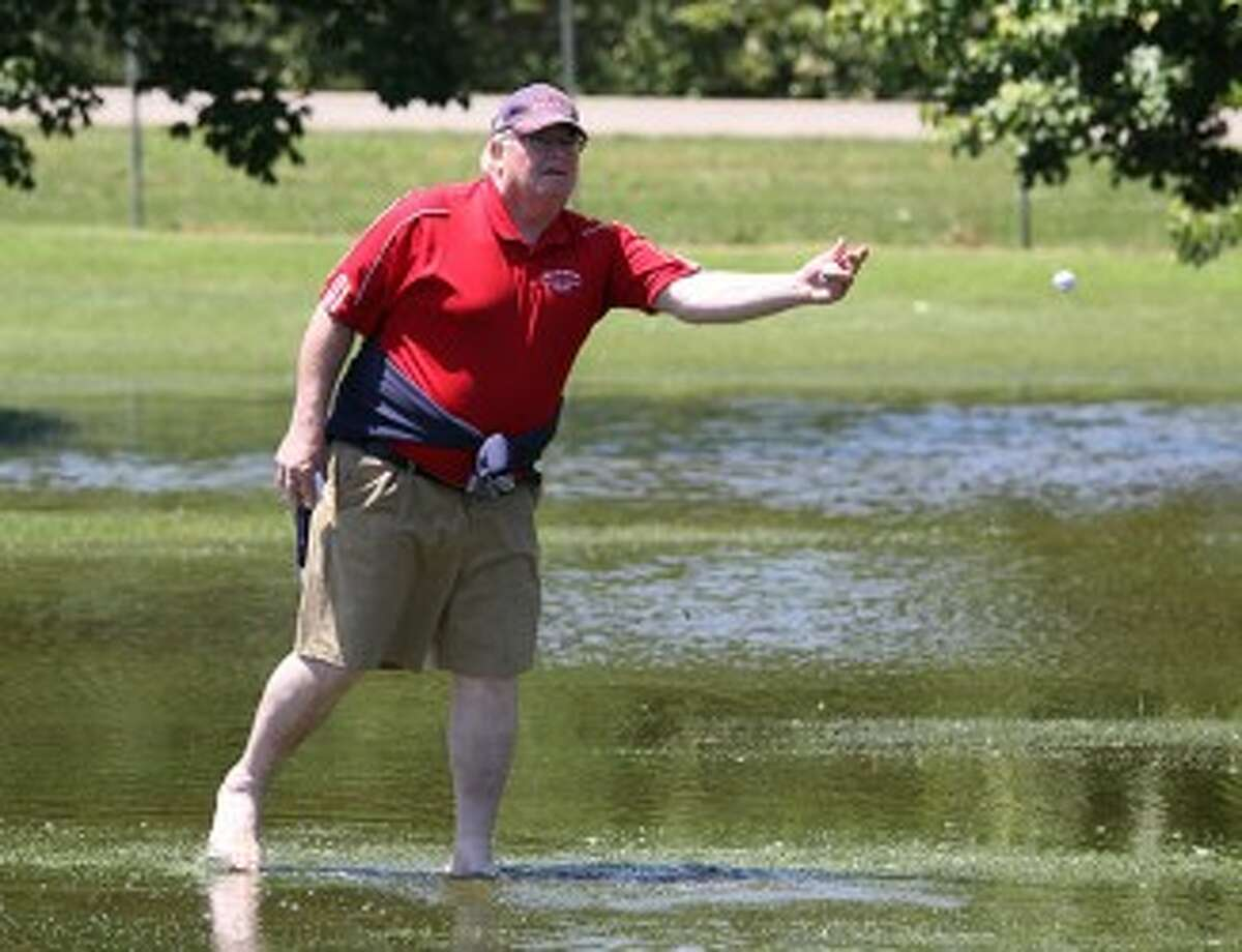 MCC assistant coach Steve Ennis retrieves a ball from a flooded fairway at Michigan State's Forest Akers East and tosses it to Zack Bialik during the Division 4 state finals in June. (Matt Wenzel/News Advocate file photo)