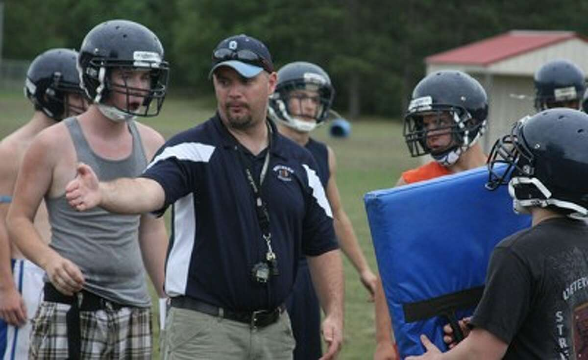 Brethren coach Alvin Rischel gives instructions to his players during the first practice of the season on Monday. (Dylan Savela/News Advocate)