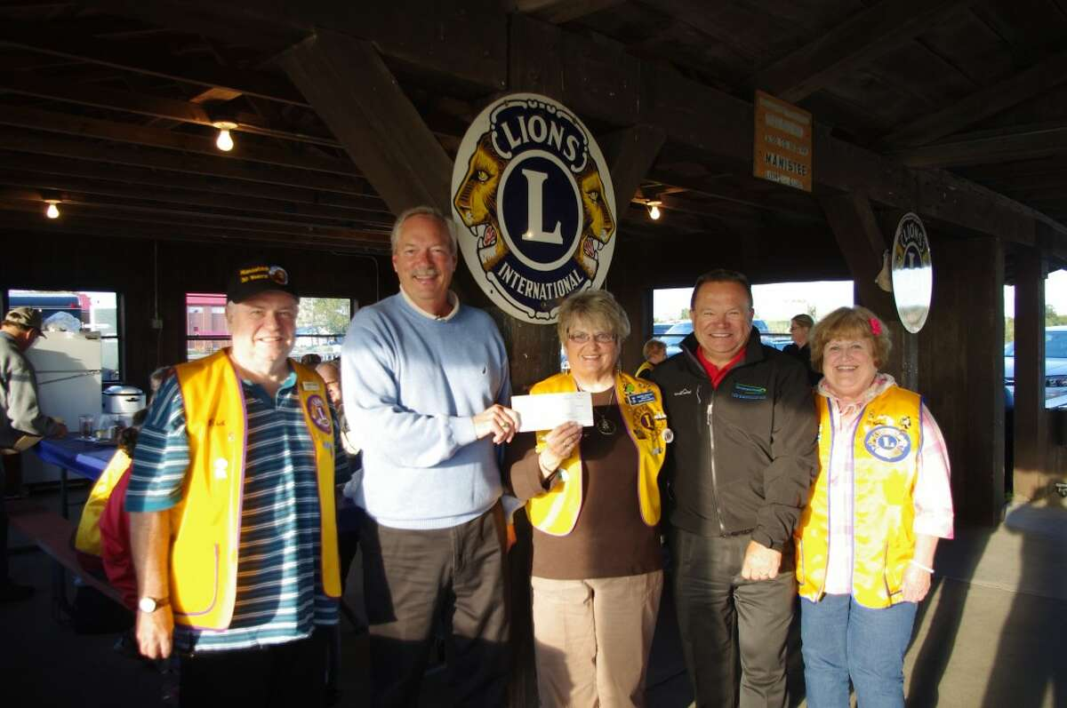 Robert Gluszewski, area manager for Consumers Energy, on Tuesday night presented a check for $5,000 from the Consumers Energy Foundation to Martha Alberts, who is coordinating the refurbishment of the Lions Club's pavilion at Douglas Park First Street Beach in Manistee. Pictured (from left to right) are Richard Veine, president of the Lions Club; Gluszewski, Alberts, Jim Pomaramski, Consumers Energy vice president of major projects construction; and Bethel Assante of the Lions Club. (Dave Yarnell/News Advocate)