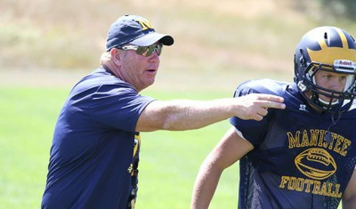 New Manistee coach Tod Miller gives instructions in front of senior Seth Pefley during the first day of padded practice on Thursday afternoon. (Matt Wenzel/News Advocate)