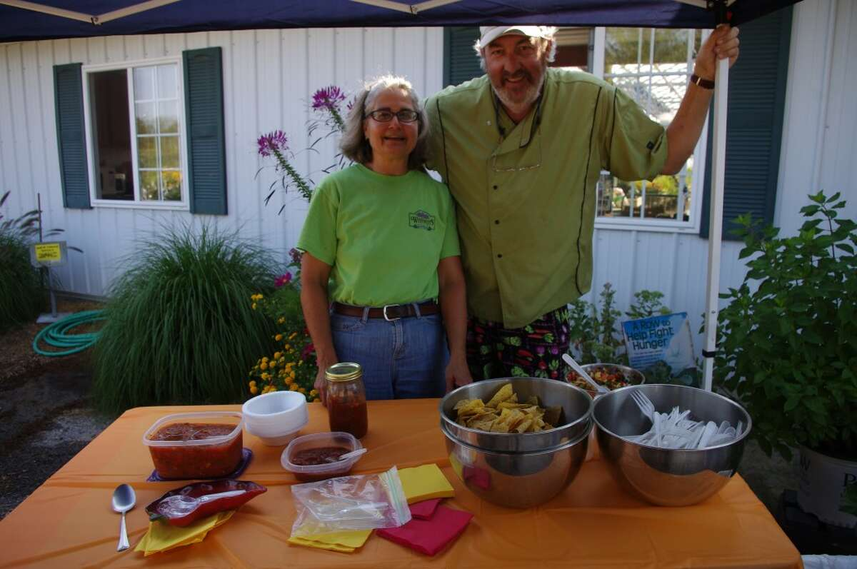 Marcie Grenmore of Weesies Brothers Garden Center and Al Frye of the Manistee Community Kitchen pose with the salsas Frye created with produce from the Manistee farmers market. (Dave Yarnell/News Advocate)