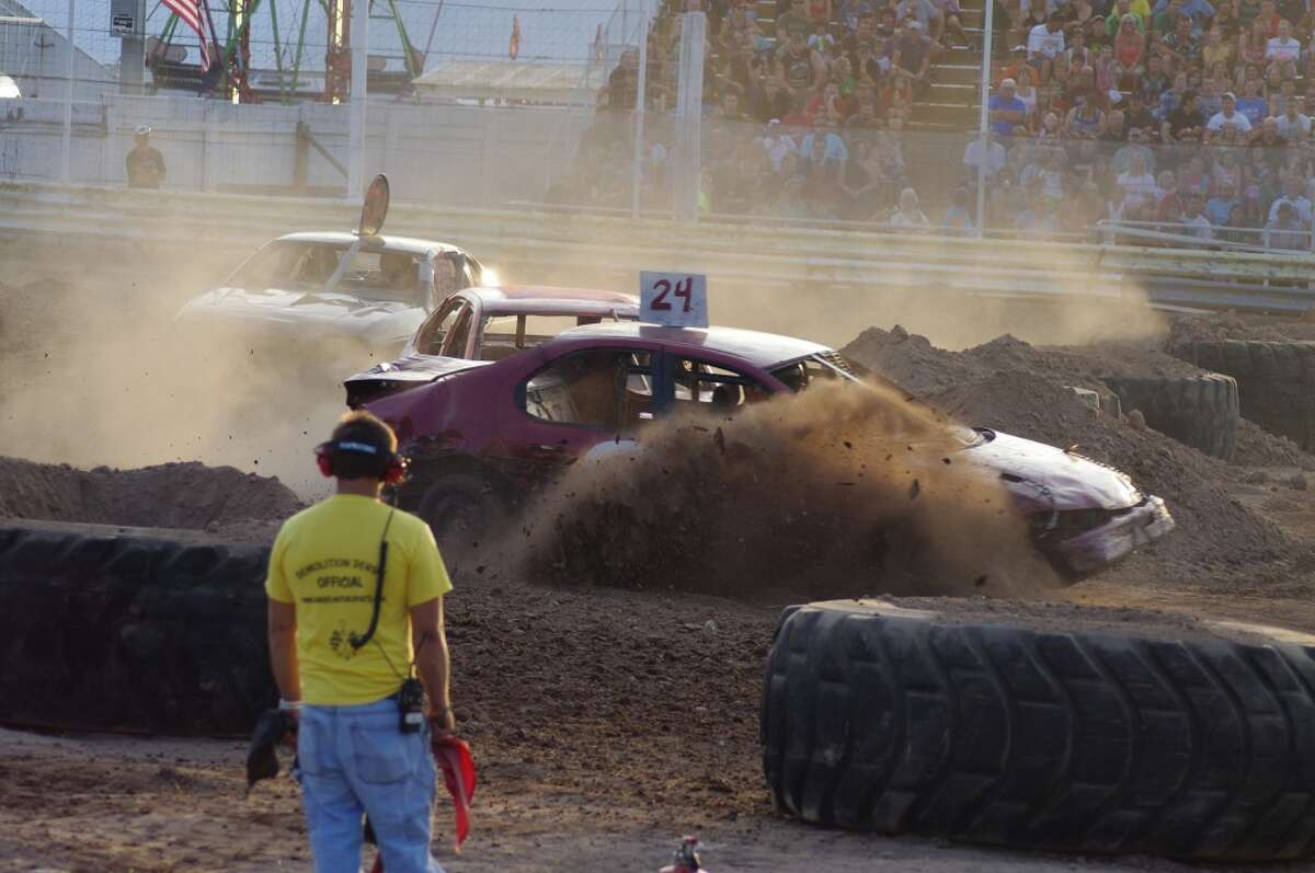 Dirt and dust flew during the figure 8 demolition derby, the final event of the 2012 Manistee County Fair. (Dave Yarnell/News Advocate)
