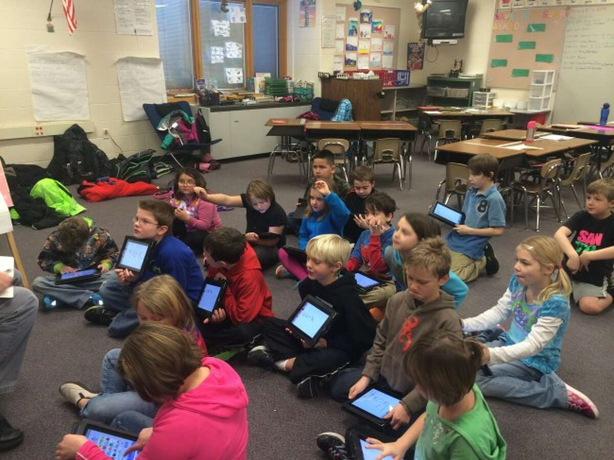 Onekama second grade students use iPads during a phonics lesson with their teacher, Ben Mauntler.