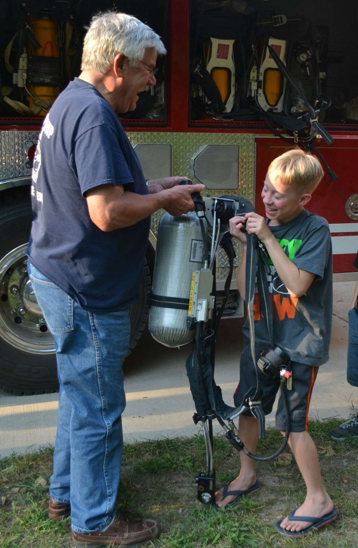 Norman Township Fire Chief John Gramza (LEFT) laughs as Tyler Duncan (RIGHT) attempts to lift a compressed air canister, a part of a firefighter's equipment that weighs between 25 and 50 pounds. (Meg LeDuc/News Advocate)