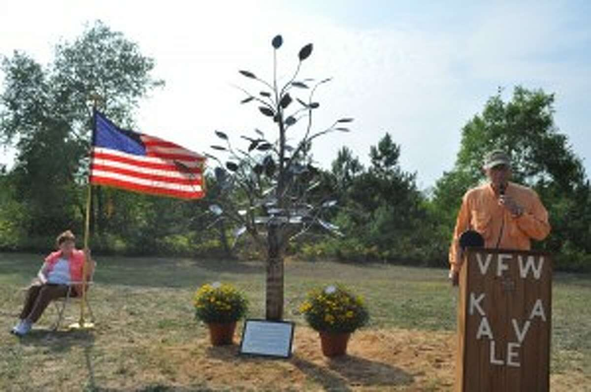 Kaleva trustee Jim Draze introduced speakers at a sculpture presentation in Kaleva ceremony on Friday. The sculpture honors three prominent citizens from Kaleva's past who made business and service contributions.