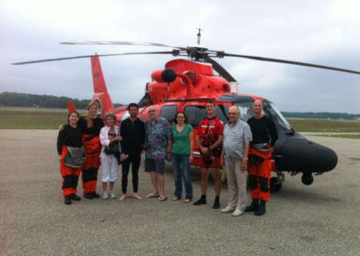 An aircrew from Coast Guard Air Facility Muskegon stands with the man they rescued from Lake Michigan and his family on Monday.