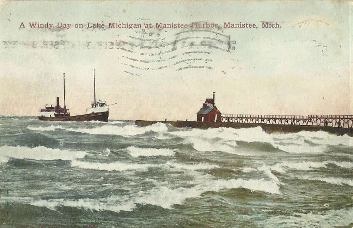 The gales of November are howling in this 1902 scene of the Manistee Harbor entrance.