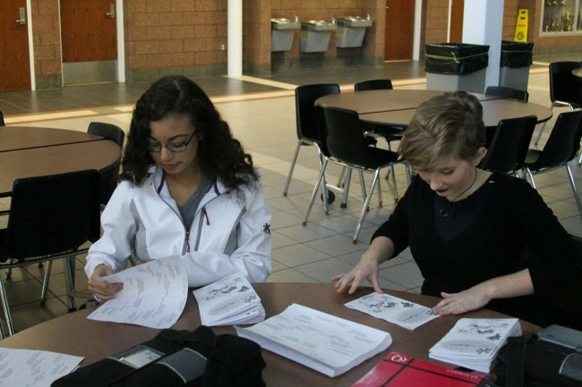 Corinne Bass and Mara Davidson fold programs for the Manistee High School Talent Show. The talent show is one of the many fundraisers students at the school have been holding for Bass who is battling Aplastic Anemia.