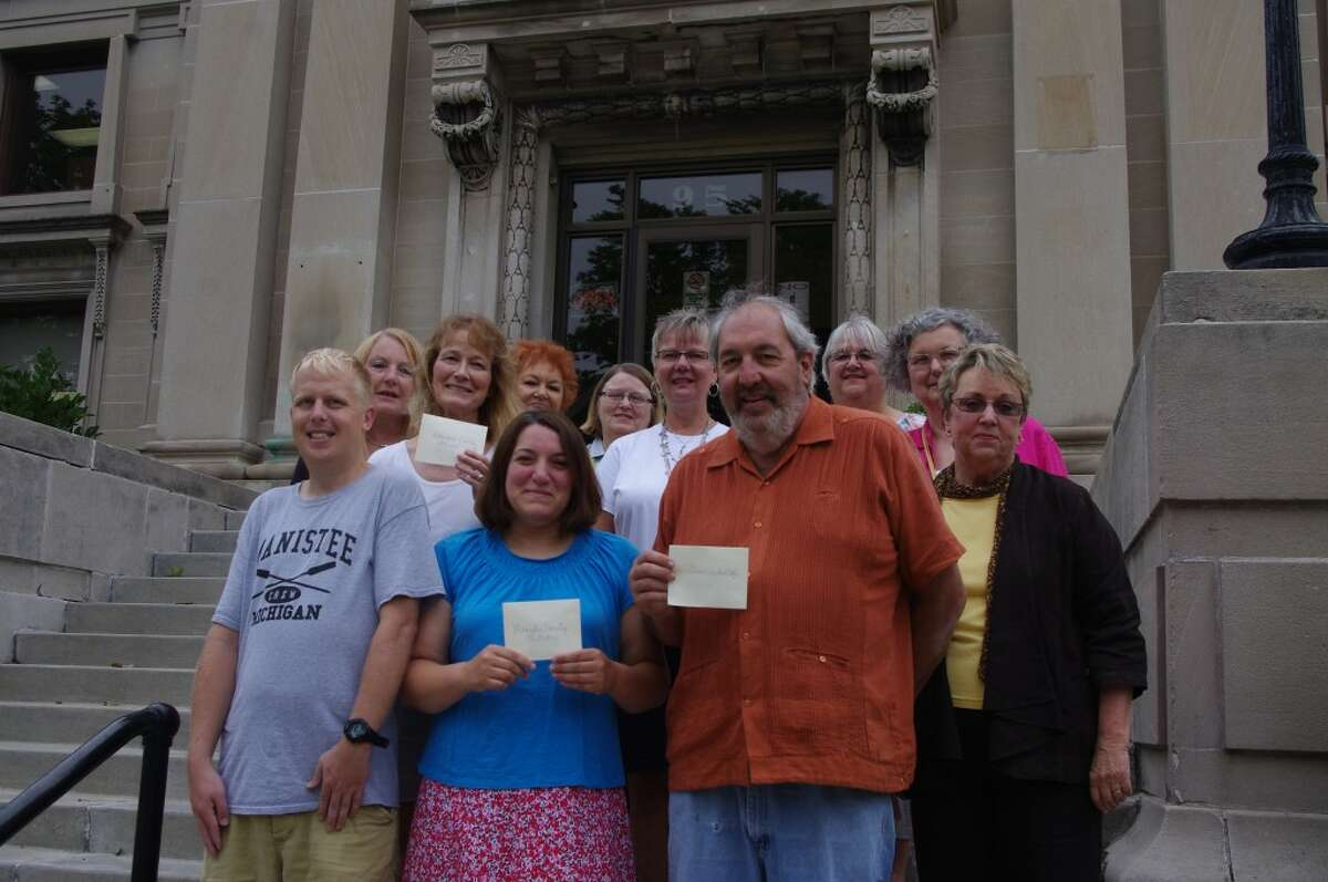Thursday of the steps of the Manistee Library the members of the Lakeside Club presented contributions to three organizations. Pictured with Lakeside Club members (from left to right) are Kent Schwandt of the Manistee Community Kitchen, Andrea Cosier of the Manistee County Library, Al Frey of the Manistee Community Kitchen, Jane Pettis, president of the Lakeside Club, (back row) Roberta Dills, Carolyn Westra representing the Manistee County Humane Society, Carol Krull, Peggy Raddatz, LaVonne Beebe, Mary Lynn Burchard and Ruth Cooper. (Dave Yarnell/News Advocate)