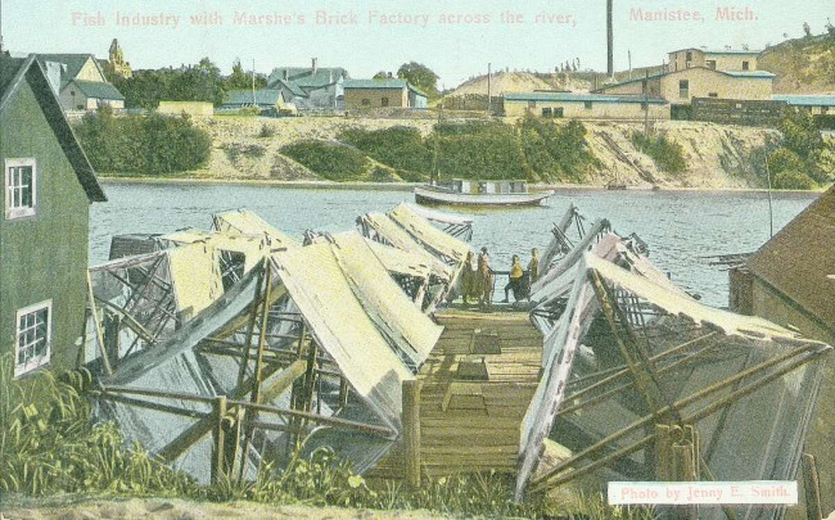 This early 1900s photograph by Jenny Smith shows the Fish Industry on the Manistee River Channel and located across the channel is the Marshes Brick Factory.