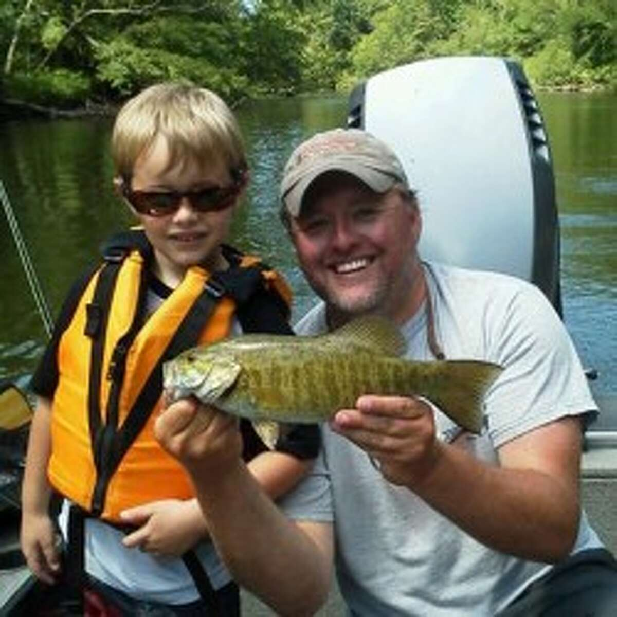 John Gouker and his son A.J. show off a smallmouth bass they caught at the Big Manistee. (Courtesy Photo)