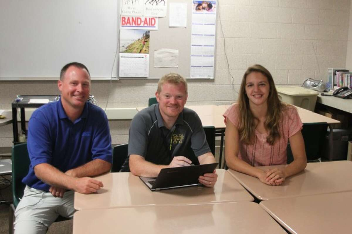Ken Grabowski/News AdvocateManistee County/Spicer Group surveyor Pat Bentley, Manistee High School teacher Eric Thuemmel and senior Jessica Gustad check out the results of the 2014 national Trig Star competition. Gustad finished first in the State of Michigan and 15th in the nation in the annual test.