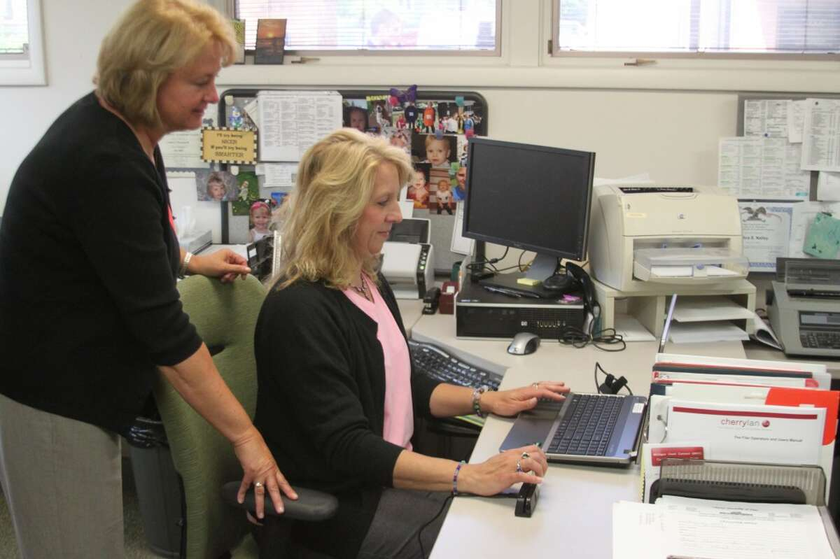 Manistee County Clerk Jill Nowak watches as deputy clerk Debra Nalley runs an identification card through the ePoll Book system. The new system was implemented throughout the county in the August election.