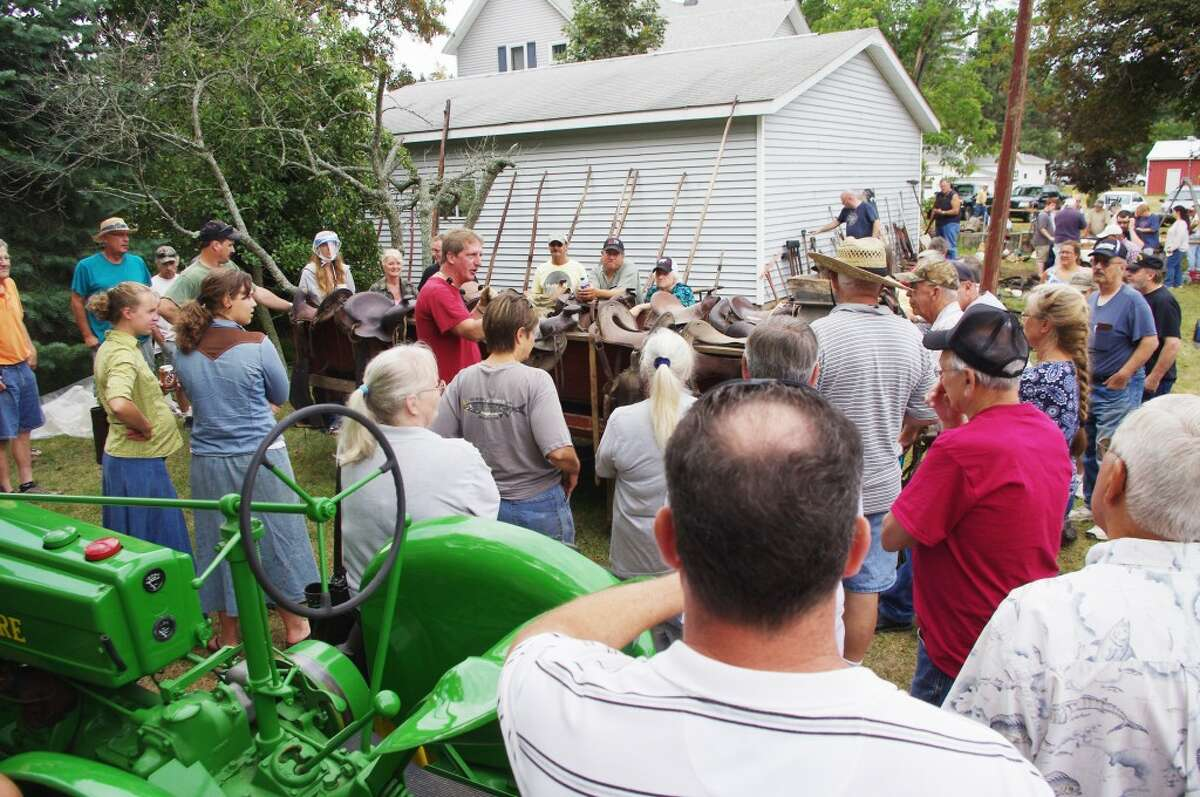 Bill Ringel (center, red shirt) was one of four auctioneers on hand to handle the auction of the Harold Kaap estate on Thursday in Parkdale. (Dave Yarnell/News Advocate)