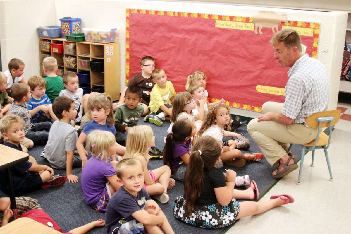Onekama Consolidated Schools kindergarten teacher James Kudlack reads his class a story during the morning of the first day in school.