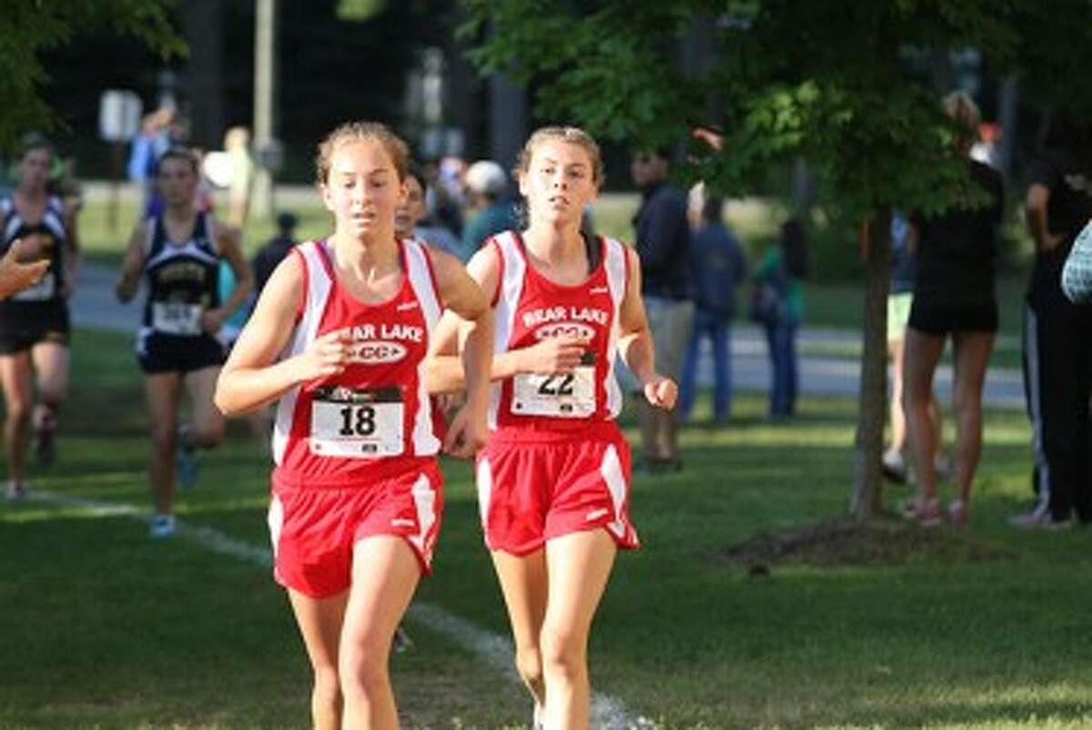 Bear Lake's Keena Gilbert (left) and Faith Moerdyk helped lead the Laker girls to a first-place finish in the small-school division of the Pete Moss Invite on Saturday at Benzie Central. (Matt Wenzel/News Advocate)