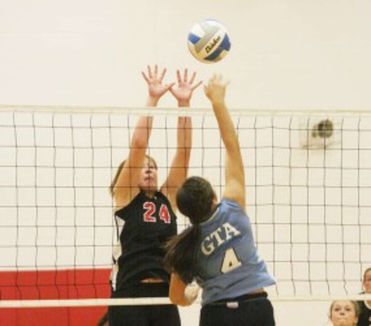 Bear Lake's Hannah Harrington (24) elevates for a block against Grand Traverse Academy's Lindsey White during Thursday's match. (Dylan Savela/News Advocate)