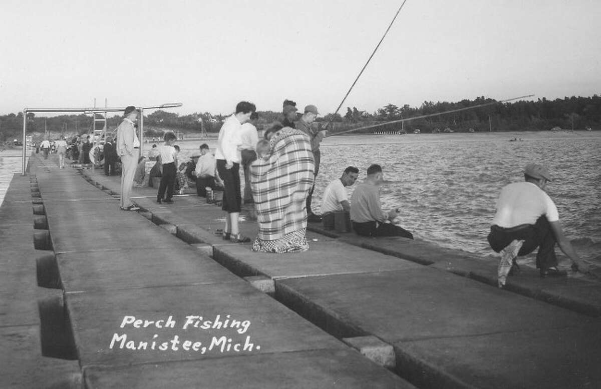 Perch fishing off the piers in Manistee was a popular thing to do in the 1950s as evident by the number of people in this photograph.
