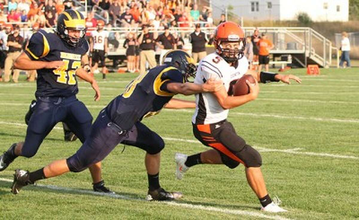 Ludington quarterback Chad Large (5) tries to escape pressure from Manistee's Adam Ball (center) and Jordan MacArthur during the first half of Thursday's game. (Matt Wenzel/News Advocate)