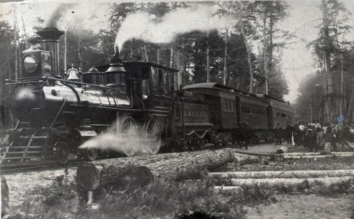 A Manistee M & NE Railroad train makes a stop to destination in Manistee County in this 1890s photograph.