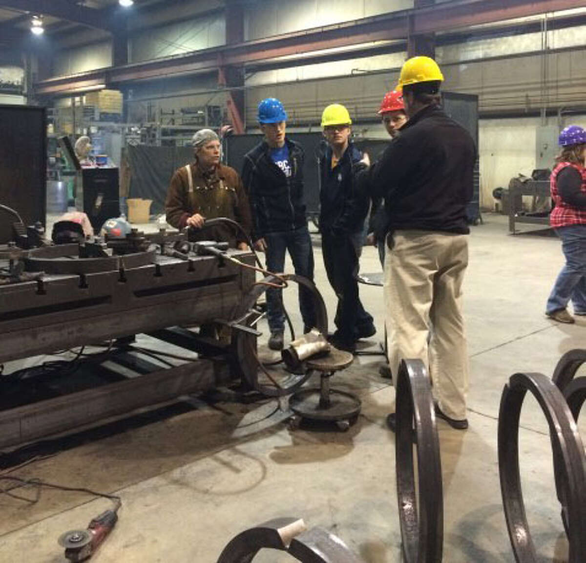 Students from Manistee County taking vocational education classes are shown touring the Metalworks factory.