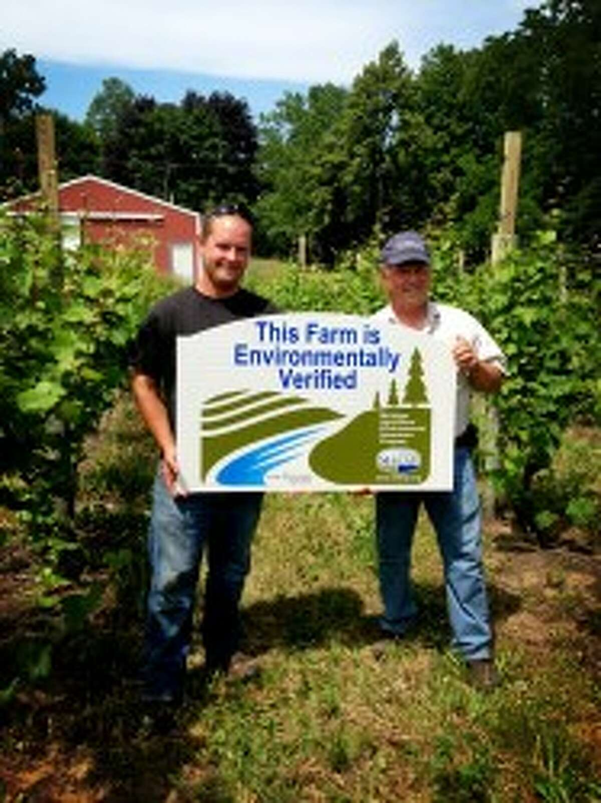 Mike and Mark Evans of Evans Brothers Fruit Company MAEAP certification sign, which shows their dedication to preserving integrity of the land they are growing on for future generations.(Courtesy photo)