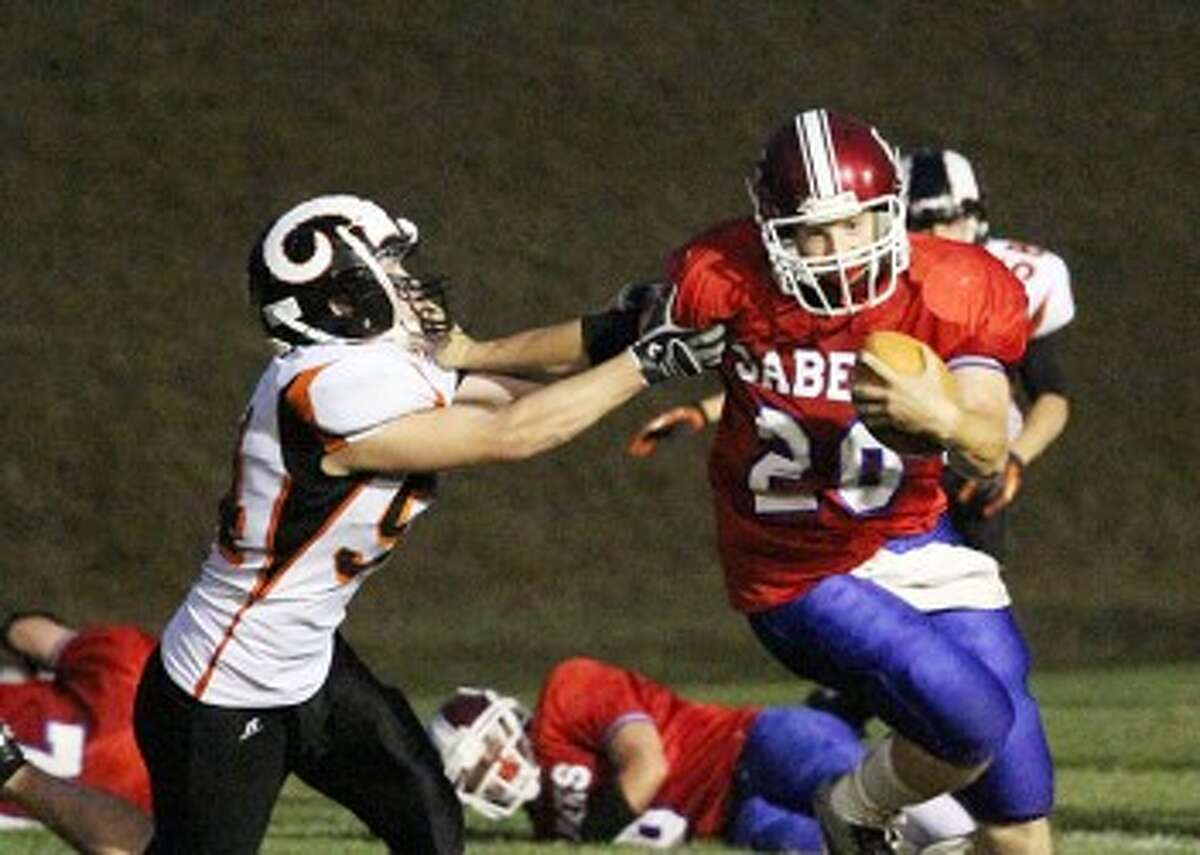 Manistee Catholic Central quarterback Ben Feliczak (20) stiff arms a Harbor Springs defender during Friday's loss. MCC on Tuesday decided to forfeit this week's game against Carson City-Crystal. (Matt Wenzel/News Advocate)
