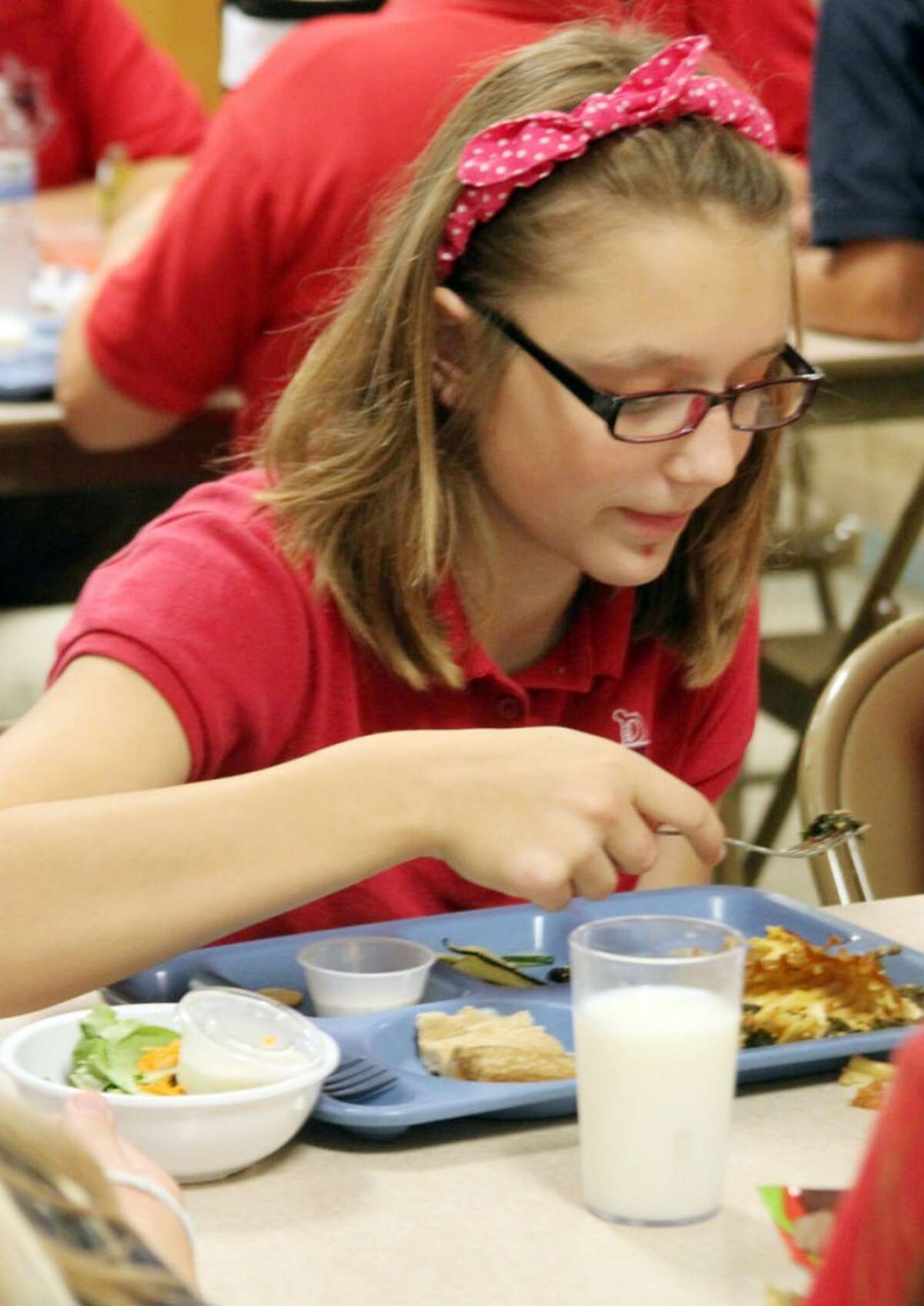 Emily Golembiewski samples the lasagna prepared by Community Kitchen staff (Meg LeDuc/News Advocate).