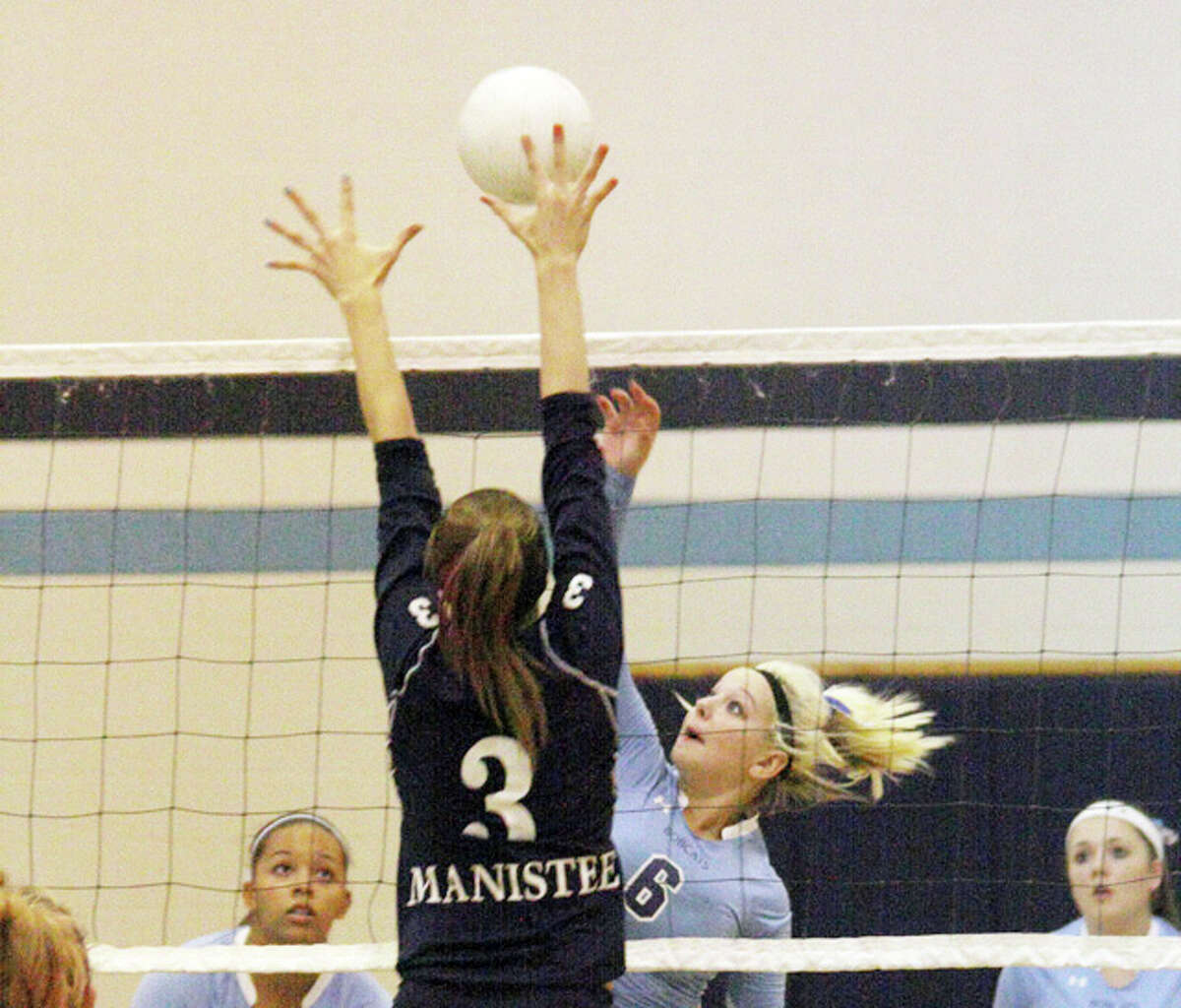 Brethren's Sarah Costello (6) spikes the ball while Manistee's Emma Burns goes up for a block during Thursday's tri-meet. (Dylan Savela/News Advocate)