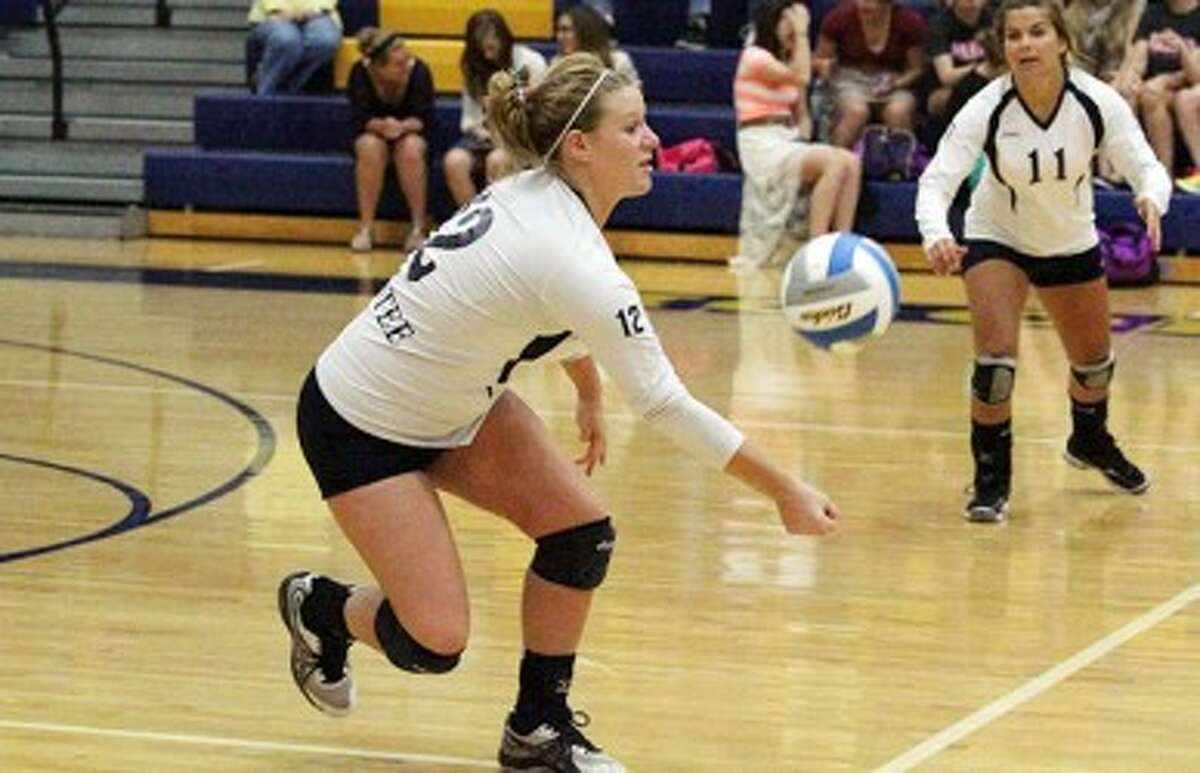 Manistee's Stephanie Johnson (12) lunges for a dig while teammate Lauren Helminski looks on during Thursday's loss to Manton. (Dylan Savela/News Advocate)