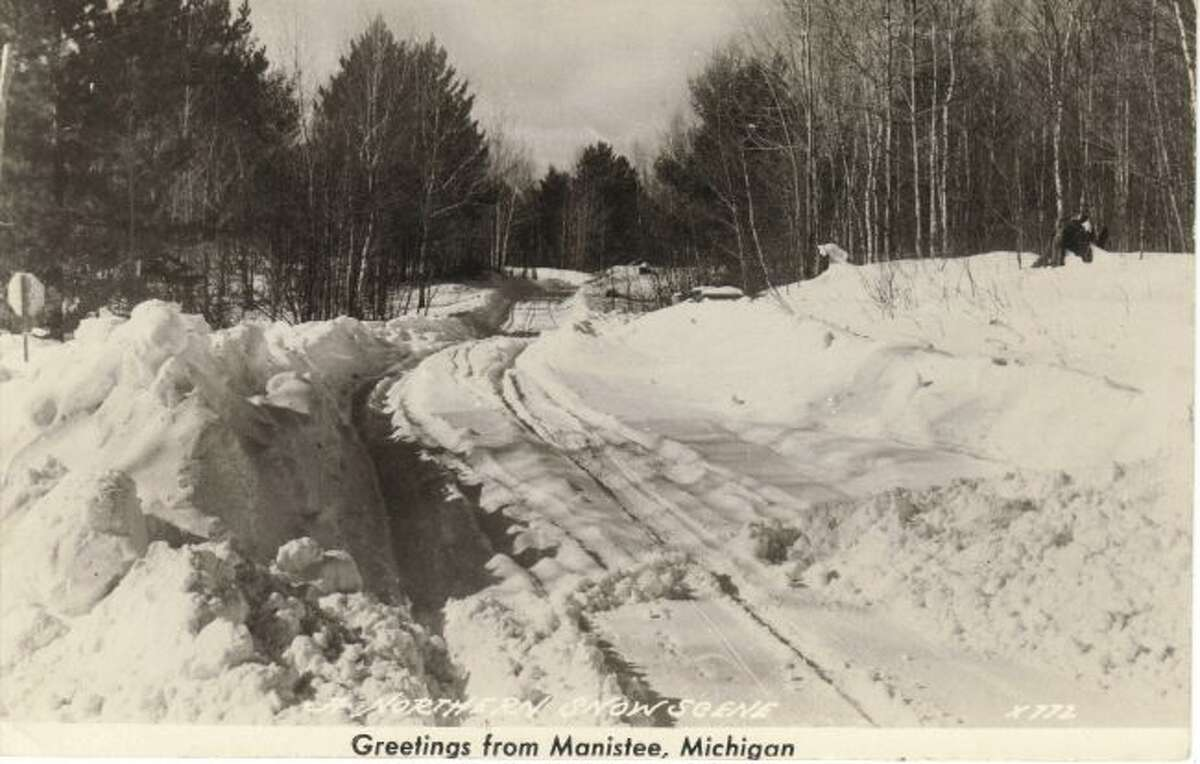 This Manistee County country road in the 1940s shows that snowplowing was not at the same same level for rural areas as it is today.