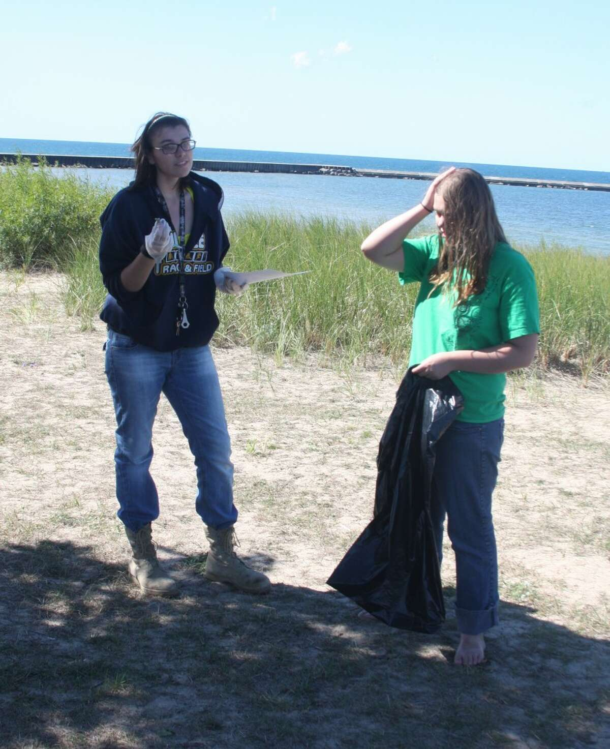 Victoria Frechette and nathalie Fisk discuss the types of things they found as part of the clean-up. The Environmental Science class students did a water study and beach clean-up as part of their studies.(Ken Grabowski/news Advocate)