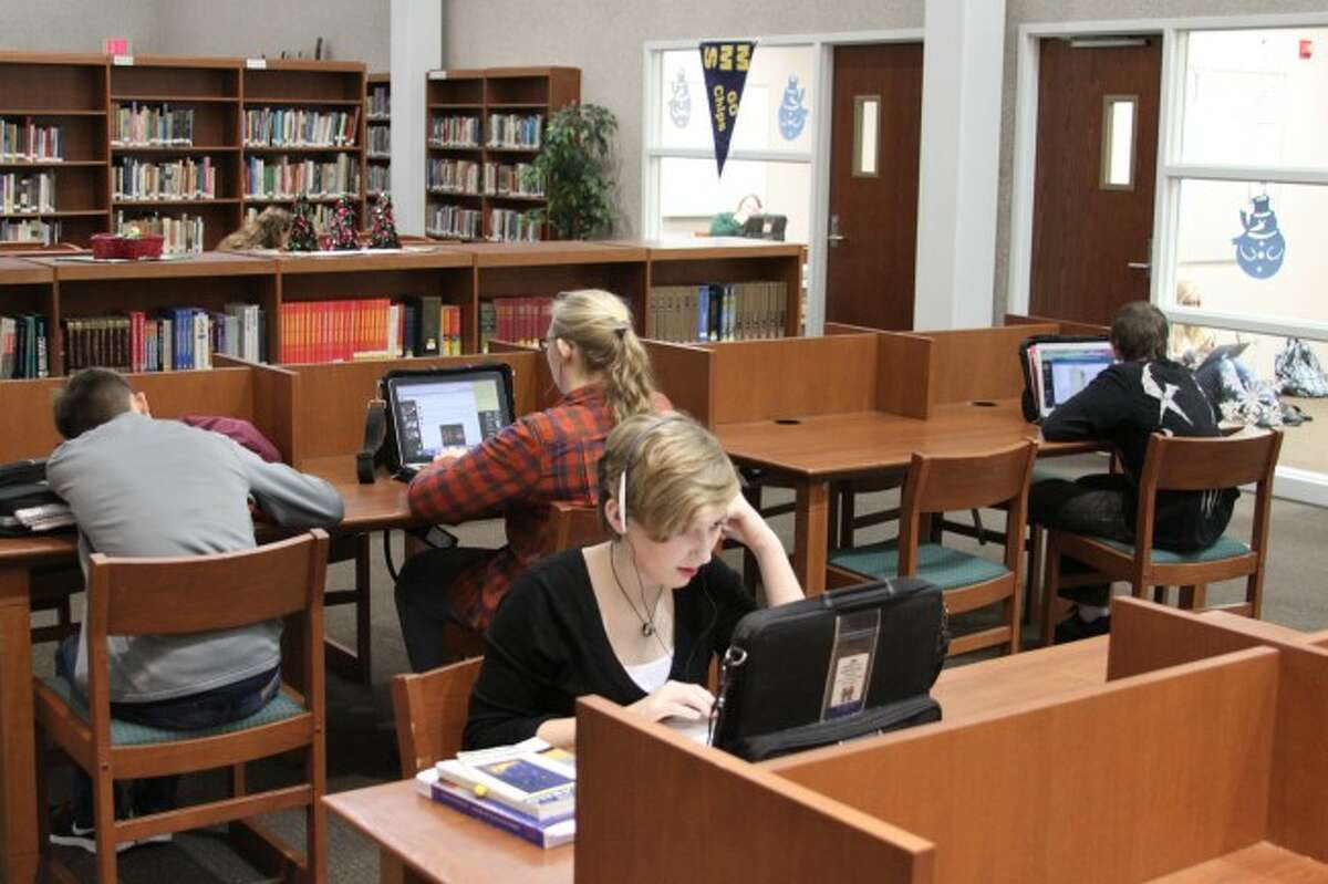 Manistee High School students utilize the technology available to them in the media center at the school with with their laptop computers. The district was recently named an Apple Distinguished School by Apple Computers.