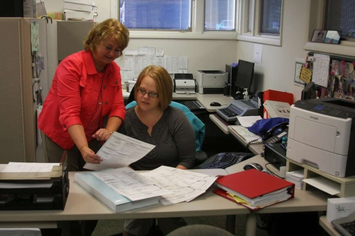 Man istee County Clerk Jill Nowak and chief deputy clerk Lindsay Marquardt look over the information for filing as a write-in candidate.