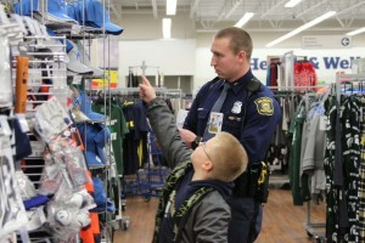 MSP Trooper Tyler Harrell participated in Shop with a Cop for the first time on Tuesday. He helped Jeremy, 7, pick out a hat for a family member.
