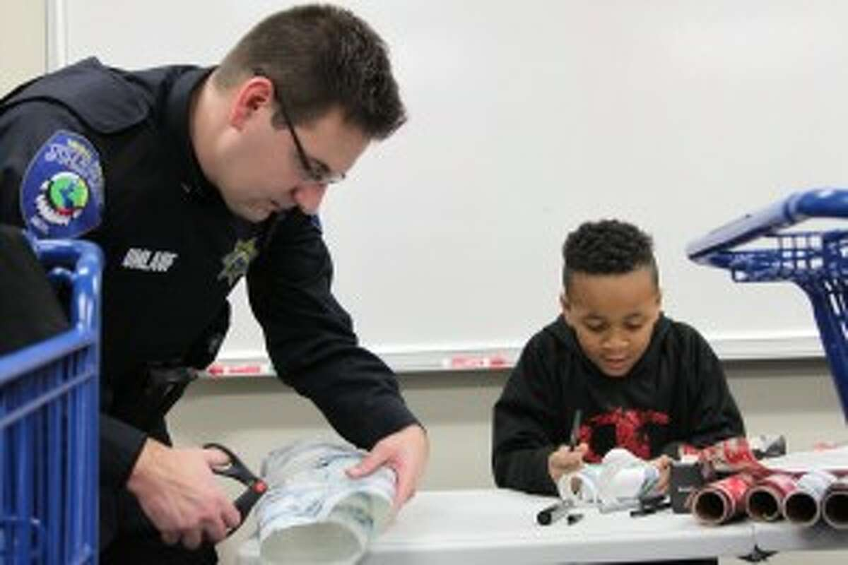 Officer Matt Umlauf, of the Little River Band of Ottawa Indians Department of Public Safety, helps Chaos Davis, 7, of Manistee, wrap his gifts during Shop with a Cop on Tuesday.