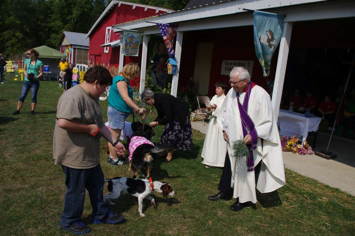 The Rev. David Selleck (right) of Manistee United Methodist Church was one of the ministers at last year's Blessing of the Animals and will also help with the program this year at Circle Rocking S Children's Farm. (News Advocate File Photo)