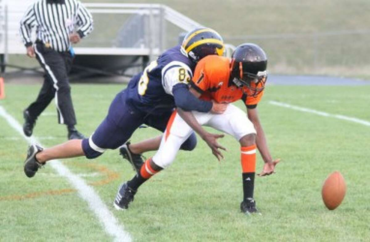 Manistee's Ben Chandler (left) tackles Muskegon Heights quarterback Ontario Porchia during the Chippewa JV team's win on Thursday night. (Matt Wenzel/News Advocate)